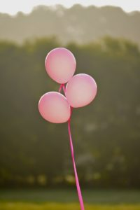 three pink balloons representing breast cancer awareness